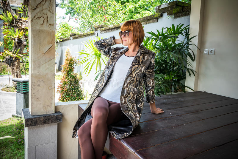 Junge Frau, Luxusmode snakeskin Pythonschlangen-Kapmantel Handgemachter snakeskin Mantel lizenzfreie stockbilder