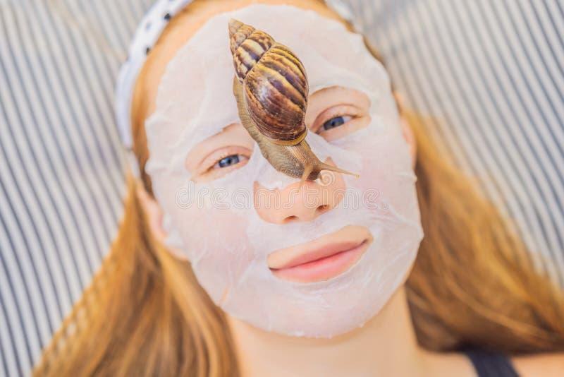 Junge Frau macht eine Gesichtsmaske mit Schneckenschleim Schnecke, die auf eine Gesichtsmaske kriecht stockbild