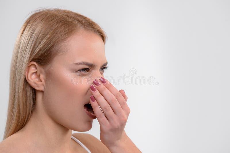 Junge Frau mag nicht ihren Atem stockfoto