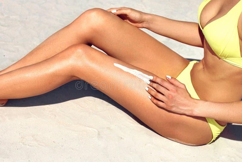 Junge Frau massiert Lichtschutzlotion beim Ein Sonnenbad nehmen am Strand Weibliches Modell w?hrend der Sommerferien stockbild