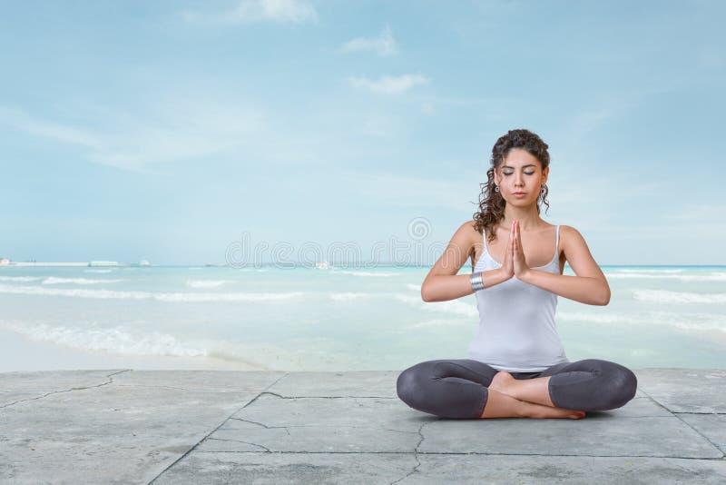 Junge Frau meditiert auf dem Strand stockbild