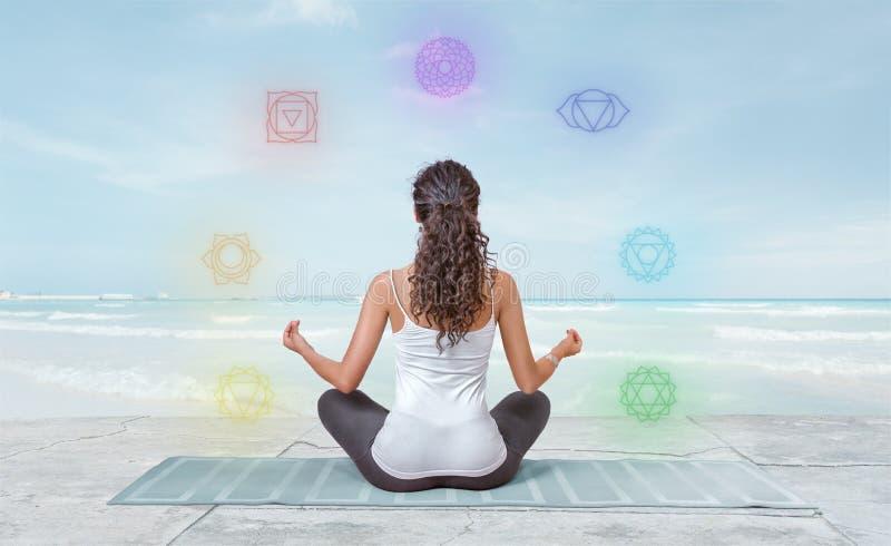 Junge Frau meditiert auf dem Strand mit den chakras, die um sie glühen lizenzfreie stockfotos