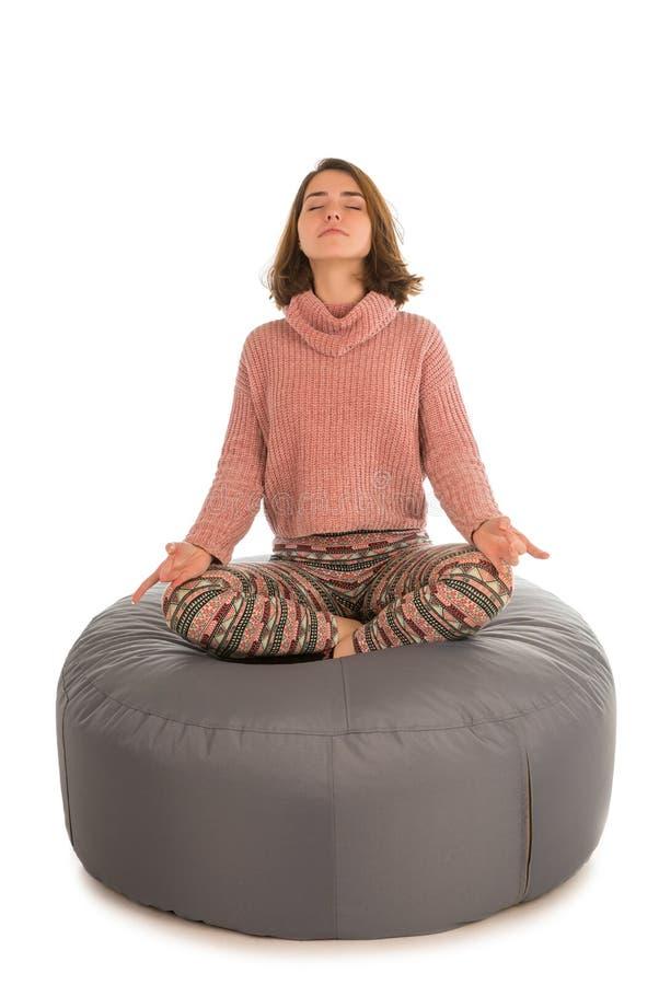 Junge Frau meditiert beim Sitzen im Lotussitz auf rou stockfotos