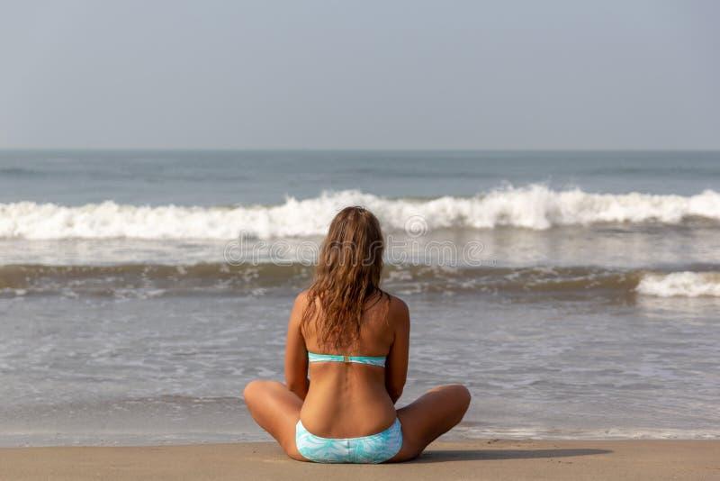 Junge Frau meditiert, sitzend auf dem Ozean lizenzfreies stockfoto