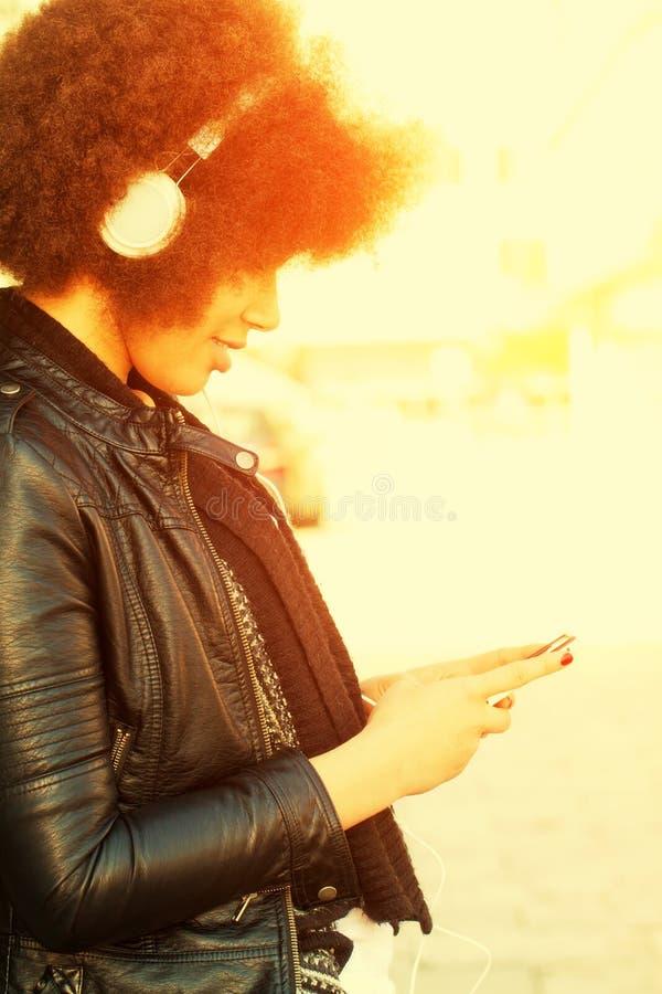 Junge Frau mit Afrohaarschnitt und -kopfhörern stockfotografie
