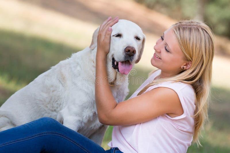 Junge Frau mit altem älterem Labrador-Hund im Park stockbilder