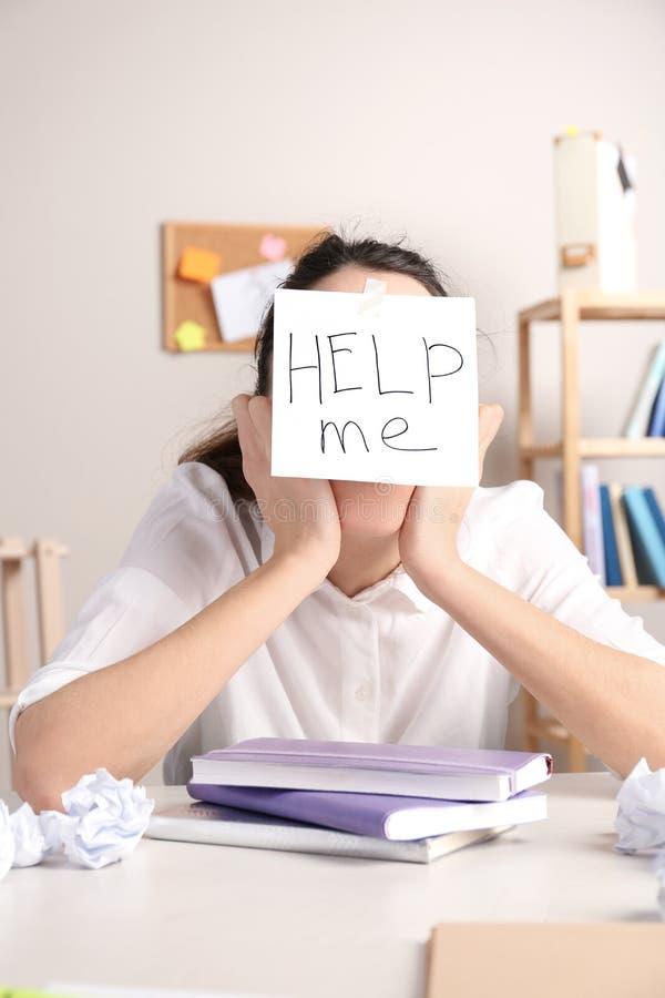 Junge Frau mit Anmerkung HELFEN MIR auf Stirn lizenzfreie stockfotos