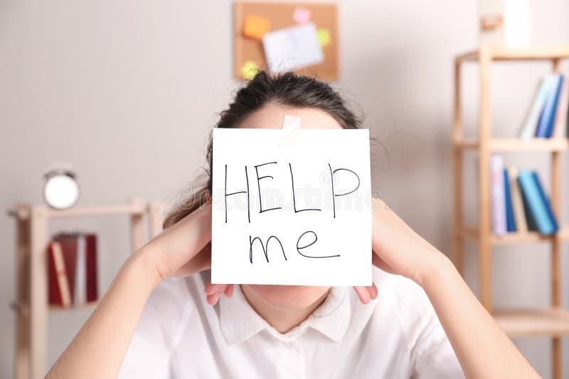 Junge Frau mit Anmerkung HELFEN MIR auf Stirn lizenzfreies stockbild