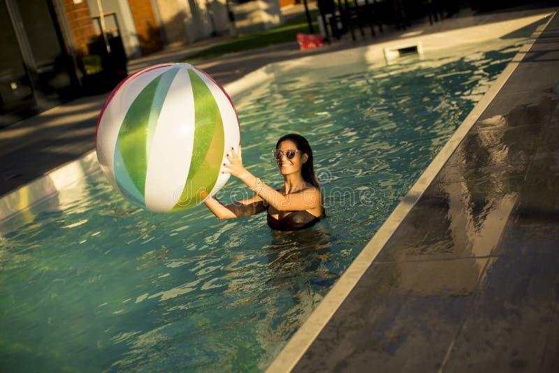 Junge Frau mit Ball im Swimmingpool lizenzfreie stockfotos