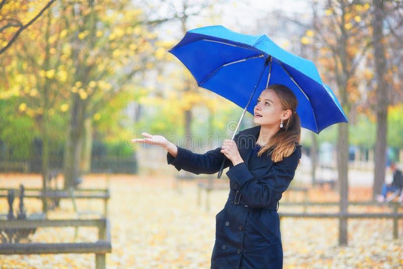 Junge Frau mit blauem Regenschirm im Luxemburg-Garten von Paris an einem regnerischen Tag des Falles oder des Frühlinges lizenzfreie stockbilder