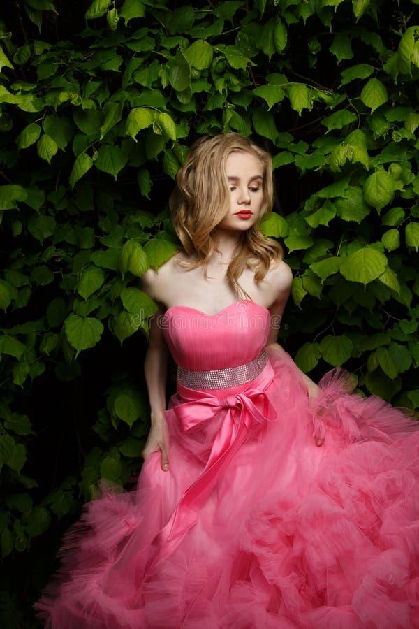 Junge Frau mit blonden Verschlüssen und dem Make-up, die rosa Abendkleid mit flaumigem Rock trägt, wirft draußen nahe dem Busch a stockbilder