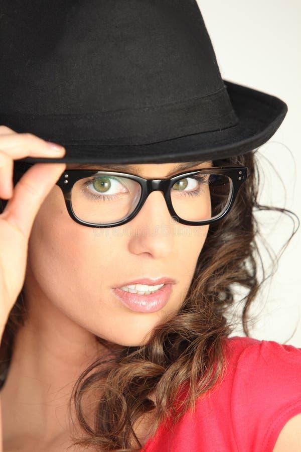 Junge Frau mit Brillen und schwarzem Hut lizenzfreie stockfotografie