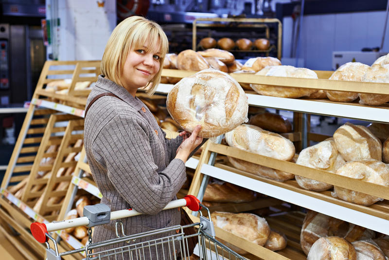 Junge Frau mit Brot im Supermarkt lizenzfreie stockfotografie
