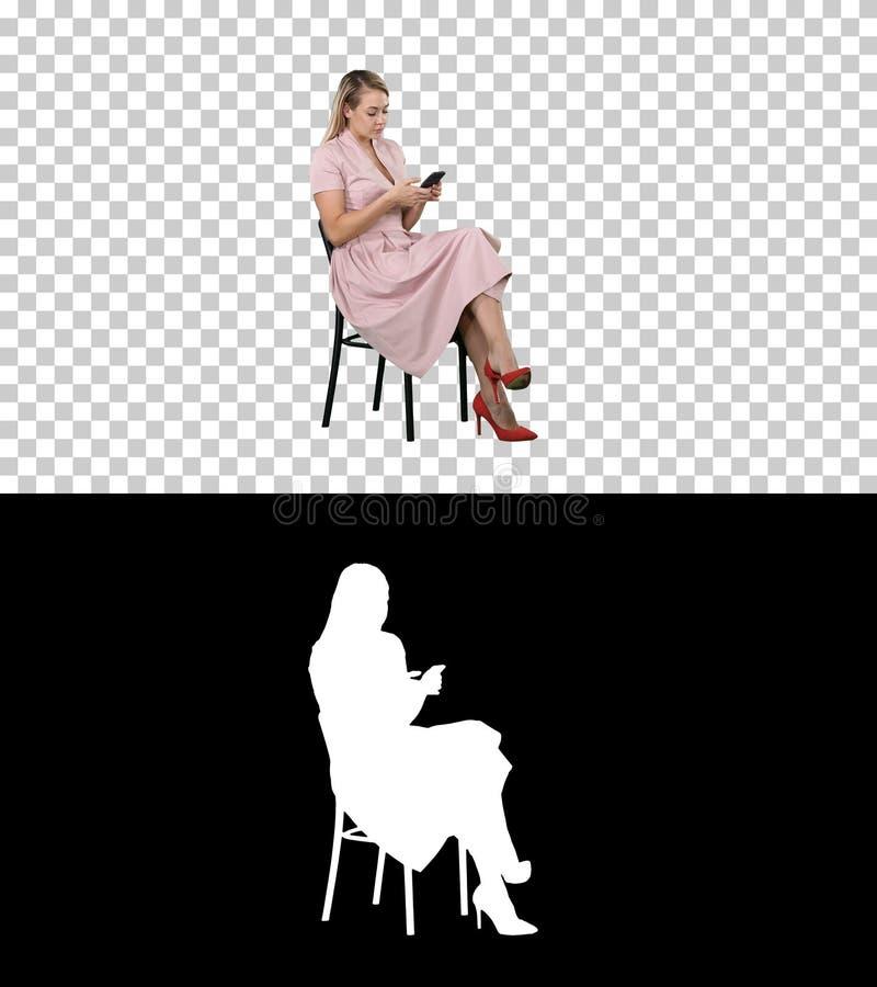 Junge Frau mit dem blonden Haar, das auf einer Stuhllesung, simsend am Handy, Alpha Channel sitzt stockbild