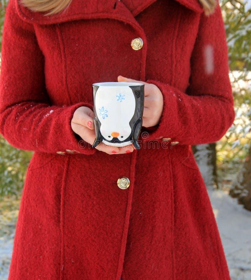 Junge Frau mit dem blonden Haar im roten Mantel, der netten Feiertagsbecher hält stockfotos