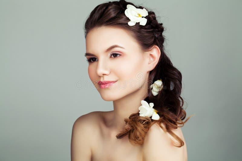 Junge Frau mit dem braunen Haar und den weißen Blumen lizenzfreies stockfoto