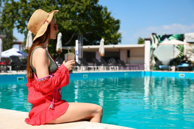 Junge Frau mit dem Cocktail, das am Swimmingpool am sonnigen Tag sich entspannt lizenzfreie stockfotos