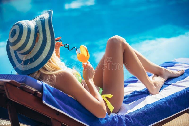 Junge Frau mit dem Cocktailglas, das in der tropischen Sonne nahe Swimmingpool auf einem Klappstuhl kühlt lizenzfreies stockfoto