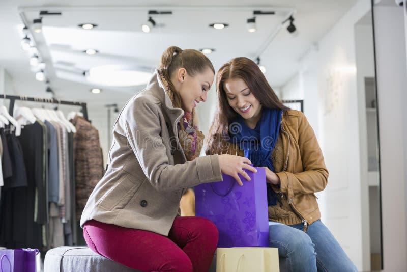 Junge Frau mit dem Freund, der in Einkaufstasche Speicher betrachtet stockfoto