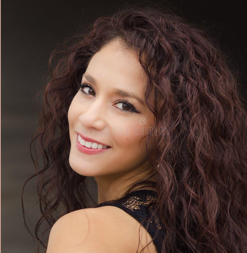Junge Frau mit dem gelockten dunklen Haar stockfotografie