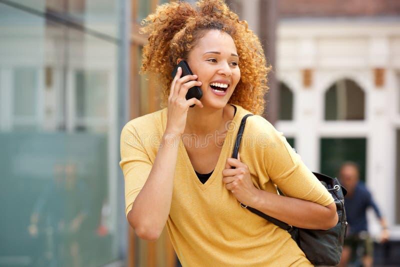 Junge Frau mit dem gelockten Haar sprechend am Handy in der Stadt lizenzfreie stockfotografie