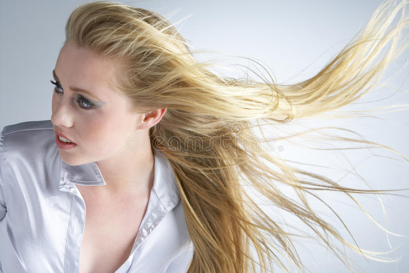 Junge Frau mit dem Haar, das nach durchbrennt lizenzfreie stockfotografie