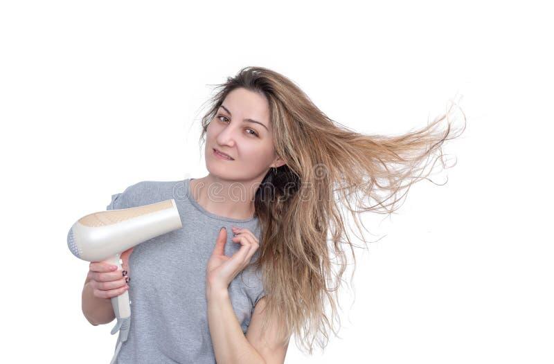Junge Frau mit dem Haartrockner, lokalisiert auf weißem Hintergrund lizenzfreie stockfotografie
