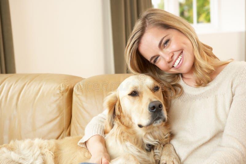 Junge Frau mit dem Hund, der auf Sofa sitzt stockfotografie