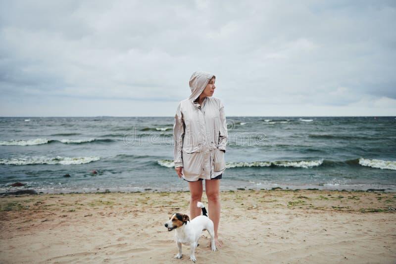 Junge Frau mit dem Hund, der weg nahes Meer schaut stockfotos