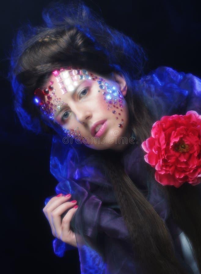 Junge Frau mit dem künstlerischen Antlitz, der große rote Blume hält lizenzfreie stockbilder