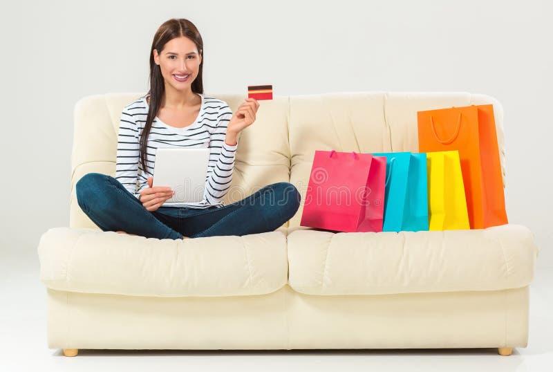 Junge Frau mit dem kaufenden Sitzen der Kreditkarte auf Sofa mit Papiertüten und neuer Kleidung lizenzfreies stockfoto