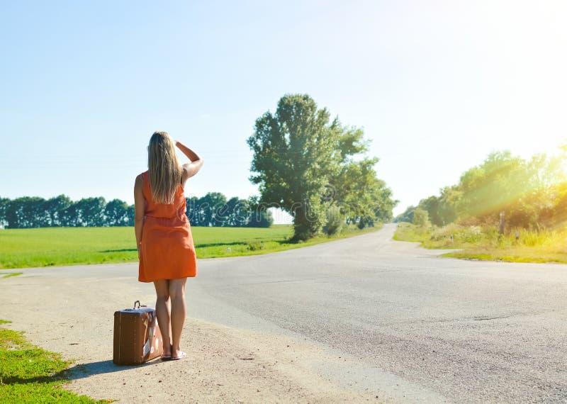 Junge Frau mit dem Koffer, der an Abstand betrachtet stockfotografie