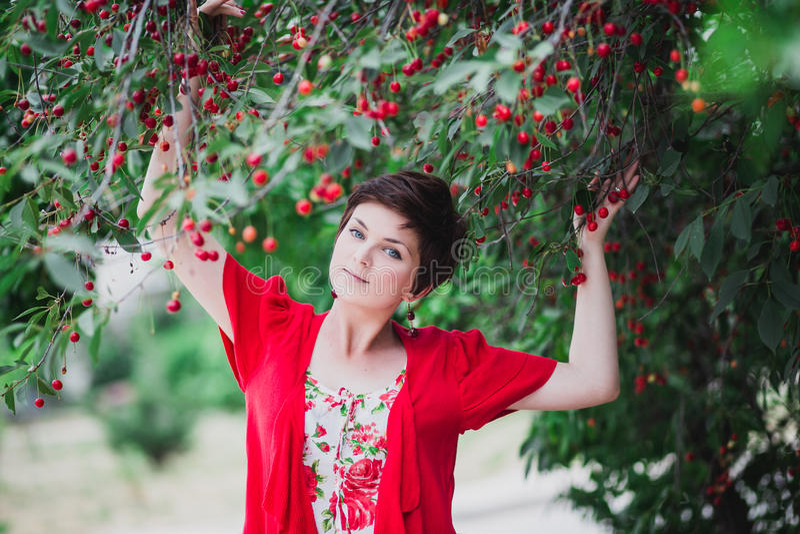 Junge Frau mit dem kurzen Haarschnitt, der nahen Kirschbaum steht lizenzfreies stockbild