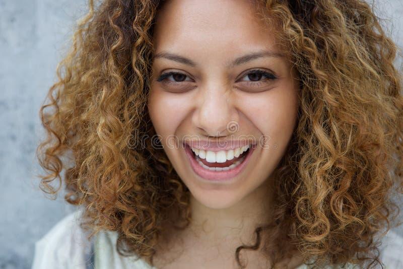 Junge Frau mit dem Lachen des gelockten Haares lizenzfreie stockfotografie