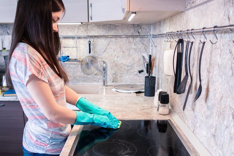 Junge Frau mit dem langen dunklen Haar säubert eine schwarze Kocherplatte stockfotografie