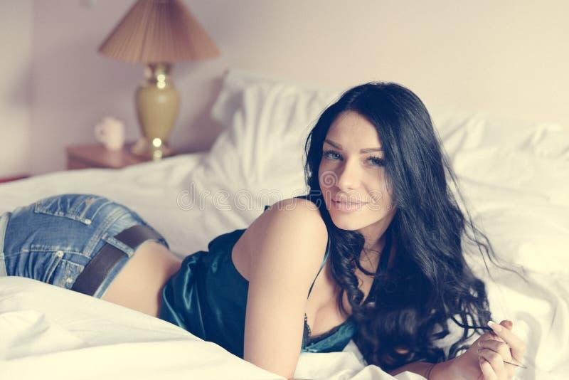 Junge Frau mit dem langen schwarzen Haar in den Jeans lächelnd und liegend auf weißem Bett u. Kamera betrachtend lizenzfreie stockfotografie