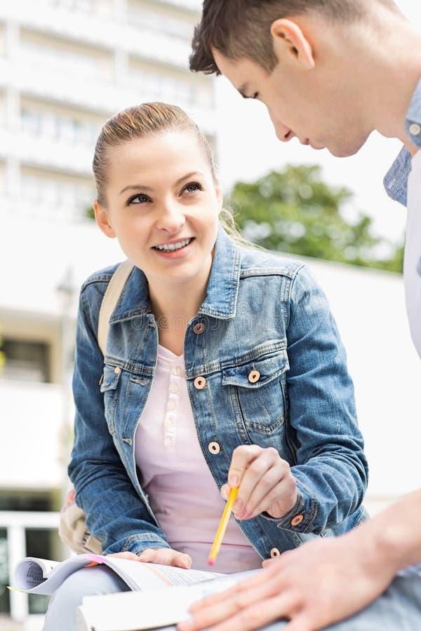 Junge Frau mit dem männlichen Freund, der zusammen am Collegecampus studiert lizenzfreies stockbild
