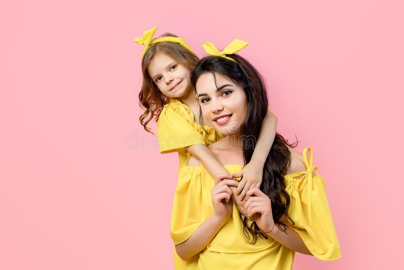 Junge Frau mit dem netten Kind, das in den gelben Kleidern aufwirft lizenzfreie stockbilder