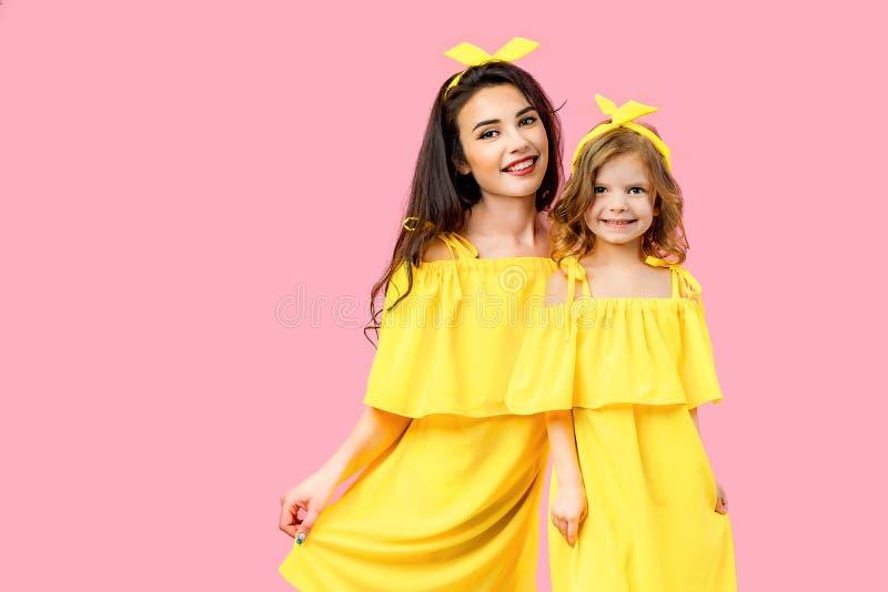 Junge Frau mit dem netten Kind, das in den gelben Kleidern aufwirft lizenzfreies stockfoto