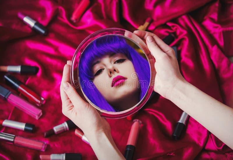Junge Frau mit dem purpurroten Haar, das in einem Spiegel schaut lizenzfreie stockfotos