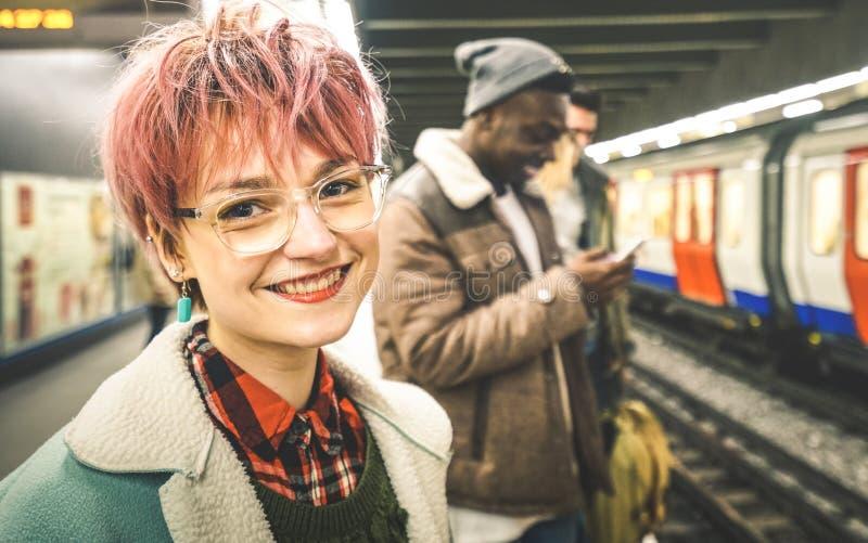 Junge Frau mit dem rosa Haar und Gruppe gemischtrassige Hippie-Freunde an der U-Bahnstation stockfotografie