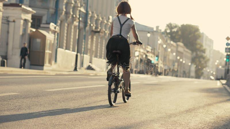 Junge Frau mit dem roten Haar, das ein Fahrrad in der Ansicht von unten des Parks reitet Frauenfahrradpark lizenzfreies stockbild
