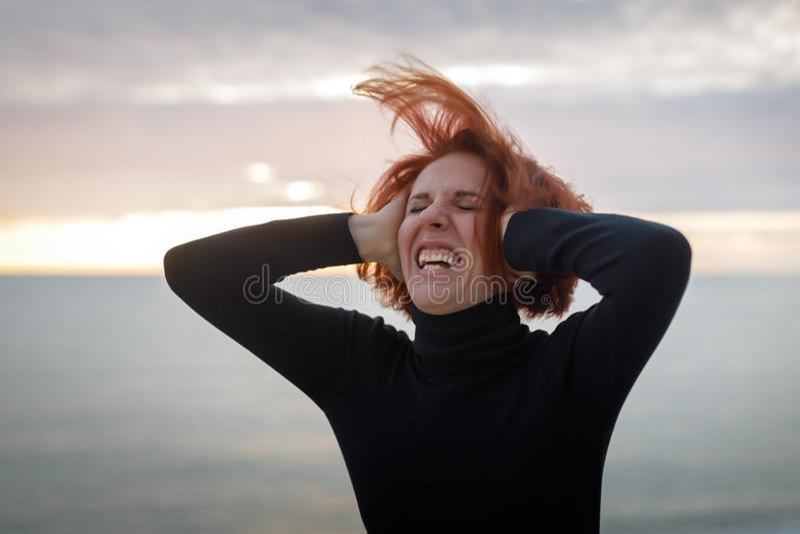 Junge Frau mit dem roten Haar, das an ihrem Kopf sich krümmt in den Schmerz auf dem Hintergrund von Meer und von Sonnenuntergang  stockfotografie