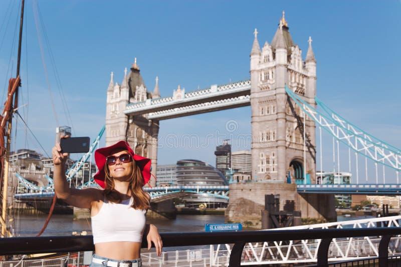 Junge Frau mit dem roten Hut, der selfie in London mit Turm-Brücke auf Hintergrund nimmt stockfotos