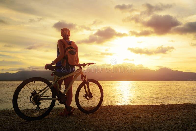Junge Frau mit dem Rucksack, der auf dem Ufer nahe ihrem Fahrrad steht stockfotos