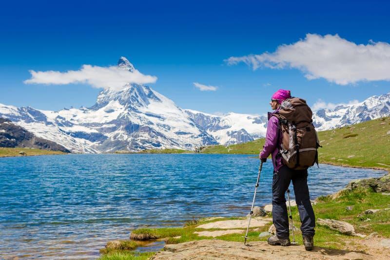 Junge Frau mit dem Rucksack, der in den Bergen wandert lizenzfreies stockbild