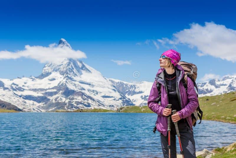 Junge Frau mit dem Rucksack, der in den Bergen wandert stockfoto