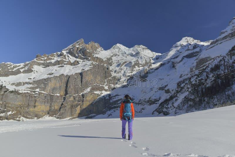 Junge Frau mit dem Rucksack, der in den Bergen wandert stockbild
