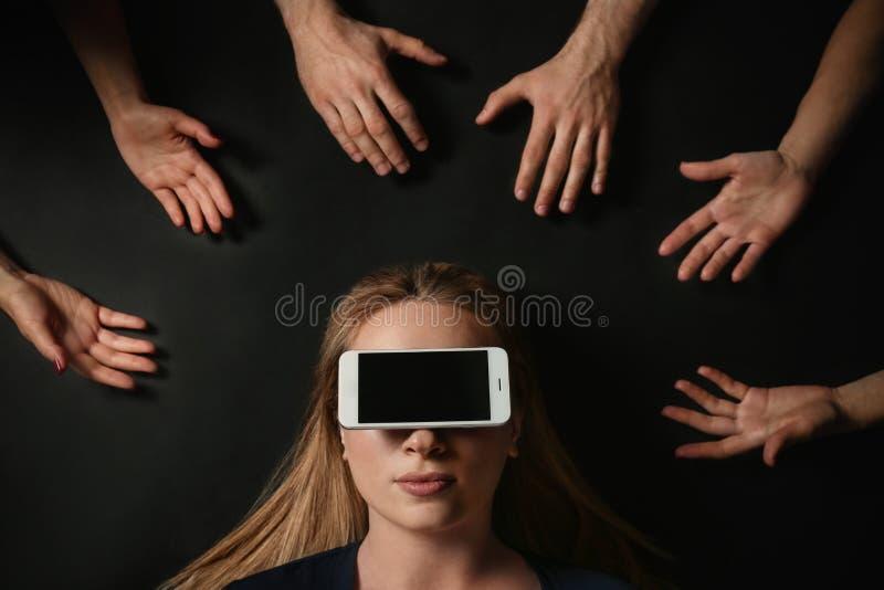 Junge Frau mit dem Smartphone, der ihre Augen surrouded durch die Hände der Leute auf schwarzem Hintergrund, Draufsicht bedeckt stockfotografie