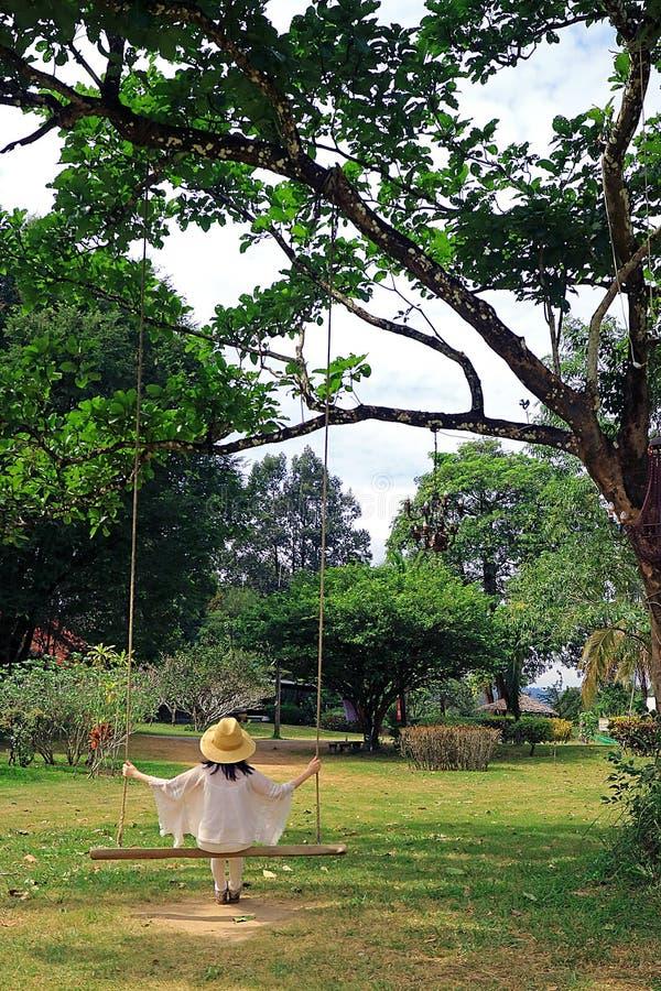 Junge Frau mit dem Strohhut, der auf einem hölzernen Schwingen im Garten sich entspannt stockfoto